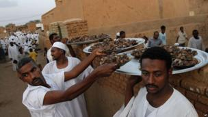 Sudanese men with plates of meat in the capital, Khartoum - Wednesday 24 July 2013