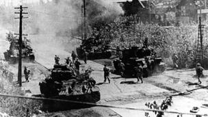 In this undated photo from North Korea's official Korean Central News Agency, distributed by Korea News Service, North Korean combatants plunge together with a tank unit into Seoul during the Korean War.