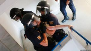 Spanish riot police drag an anti-eviction activist down a staircase in Madrid