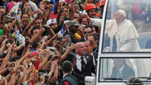 Pope Francis greets the crowd of faithful from his popemobile in downtown Rio de Janeiro