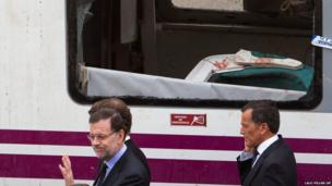 Spanish prime minister Mariano Rajoy, left, walks next to a derailed car at the site of a train accident in Santiago de Compostela, Spain,