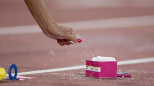America's Jennifer Suhr grabs chalk in preparation for a pole vault