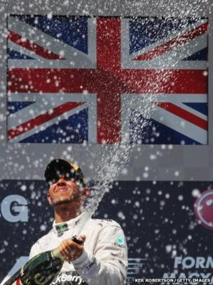 Lewis Hamilton of Great Britain and Mercedes GP celebrates on the podium after winning the Hungarian Formula One Grand Prix