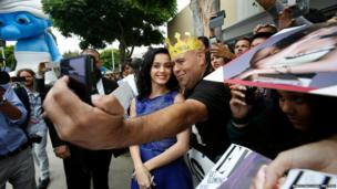 Singer Katy Perry poses with fans at the premiere of The Smurfs 2 in Los Angeles