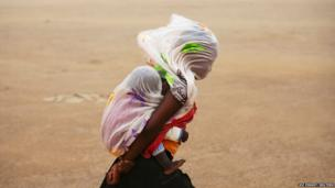 A woman carrying her baby and wrapped with a shawl walks through a sandstorm in Timbuktu, Mali
