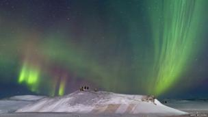 An auroral display above photographers.