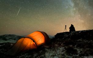 A photographer camping out in a remote location and spending hours waiting for the perfect shot of the night sky.