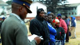 A policeman stands as Zimbabweans line up near a polling station in Harare to vote in a general election on 31 July 2013