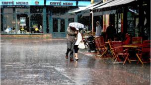 Couple under an umbrella in downpour