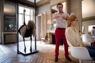 A customer is having a hair cut by Australian hair designer David Mallet