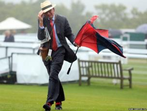 A racegoer struggles with wet and windy conditions during day one of Glorious Goodwood