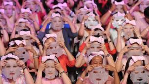 Participants get ready to apply facial masks on their faces in Taipei
