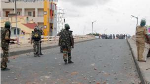 United Andhra Pradesh activists (background) throw stones towards police as they demonstrate against the formation of Telangana state in Anantapur,