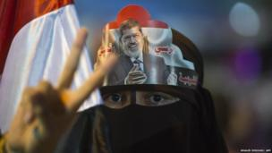"A female supporter puts Egypt""s deposed president Mohamed Morsi portrait on her head during sit in outside Rabaa al-Adawiya mosque in Cairo on August 1, 2013."
