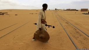 A man from the Hadandawa tribe walks across railway tracks covered by sand as a result of desert encroachment at Ogrein Railway Station at the Red Sea State in Sudan.