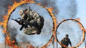 "A soldier from the People""s Liberation Army jumps through a ring of fire as part of training during the PLA Army Day in Wenzhou, Zhejiang province."