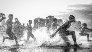 """National Geographic Traveler Photo Contest Grand Prize winner Wagner Araujo's image """"Dig Me River"""" shows boys running into the Rio Negro river in Brazil."""