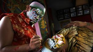 Performers in Taiwan prepare by painting their faces like fierce bright masks for Guanjiang Shou.