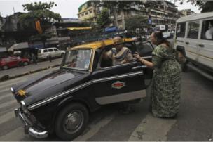 Customers getting inside a Premier Padmini taxi in Mumbai.