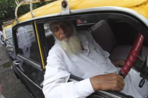 an Indian taxi driver poses for photos from inside his vehicle in Mumbai, India
