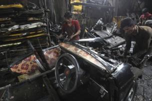 Indian workers dismantle a Mumbai Premier Padmini taxi in a scrap yard, in Mumbai