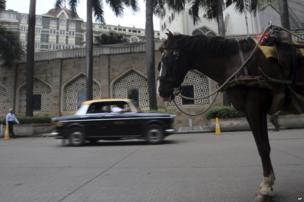 A Premier Padmini taxi rides past a horse drawn carriage in Mumbai