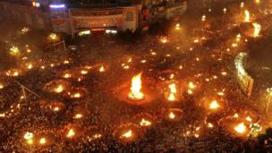 Crowds of people in China from the ethnic Yi minority celebrate with visitors during their Torch Festival in Xichang.