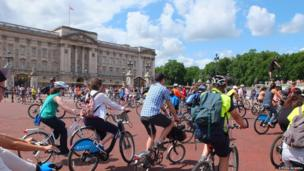 Cyclists ride past Buckingham Palace. Photo: Steven Russell