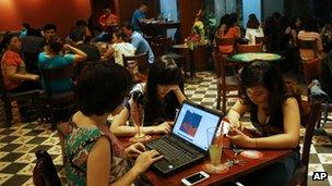 File photo: Three Vietnamese girls use a laptop and smart phones to go online at a cafe in Hanoi, Vietnam, on 14 May 2013