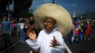 A man dressed as a Honduran peasant takes part in the El Correo parade on 1 August 2013