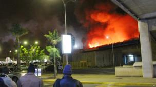 People watch a large blaze raging at the Jomo Kenyatta International Airport in Nairobi, Kenya, early Wednesday 7 Aug 2013.