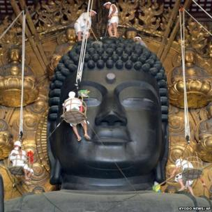 Buddhist monks and parishioners clean the giant statue of Buddha at the Todaiji temple in Nara, western Japan