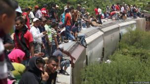 Central American immigrants arrive on top of a freight train in Ixtepec, Mexico