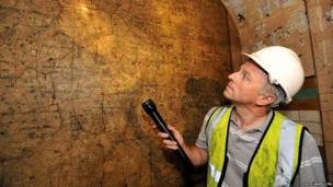 Ministry of Defence property surveyor Julian Chafer looks at the detail of an old map of London at Brompton Road tube station