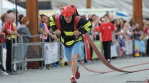 Fire fighters taking part in the Ultimate Fire fighter competition at Titanic Slipway in Belfast