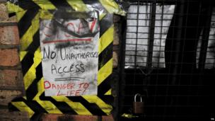 A makeshift warning sign next to the locked gateway leading to the platforms of the former Brompton Road tube station.