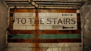 """A view of a """"to the stairs"""" sign inside the former Brompton Road tube station."""