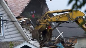 A digger destroys the house of Ariel Castro, where he kept three women captive for over a decade