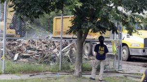 An FBI agent watches as the house where three women were held captive and raped for more than a decade is being demolished on Wednesday, 7 August, 2013, in Cleveland