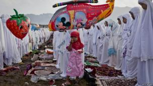 "A girl eats ice cream as Indonesian Muslims perform Eid Al-Fitr prayer on ""sea of sands"" at Parangkusumo beach in Yogyakarta, Indonesia (8 August 2013)"