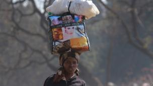 A woman carries her luggage in central, Harare, Thursday 8 August, 2013.
