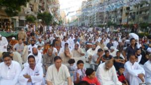 Men sat gathered in the streets for Eid prayers in Egypt. Photo: Hosni Ragab