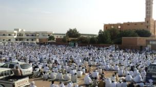 Men mostly dressed in traditional white robes sit outside mosque in Sudan during Eid prayers. Photo: Amer Abou Zeid