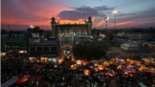 Indian Muslims shop ahead of Eid al-Fitr in front of Mecca masjid in Hyderabad, India.