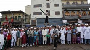 A tightrope walker performs while holding a balancing pole in the old quarters of Delhi on Eid al-Fitr