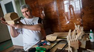 Ukrainian Dmitry Balandin assembles a wooden model of a Cylon
