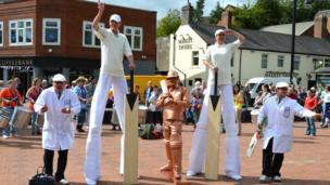 Stilt walkers with others