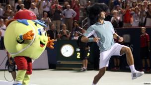 Novak Djokovic dancing with a mascot