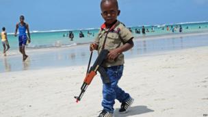 Somali boy carrying a toy gun on Lido beach, Mogadishu, Somalia - Thursday 8 August 2013