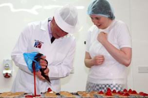 The Prince of Wales helps bakery worker Lauren MacKenzie make strawberry tarts on a visit to Reid's bakery in Thurso